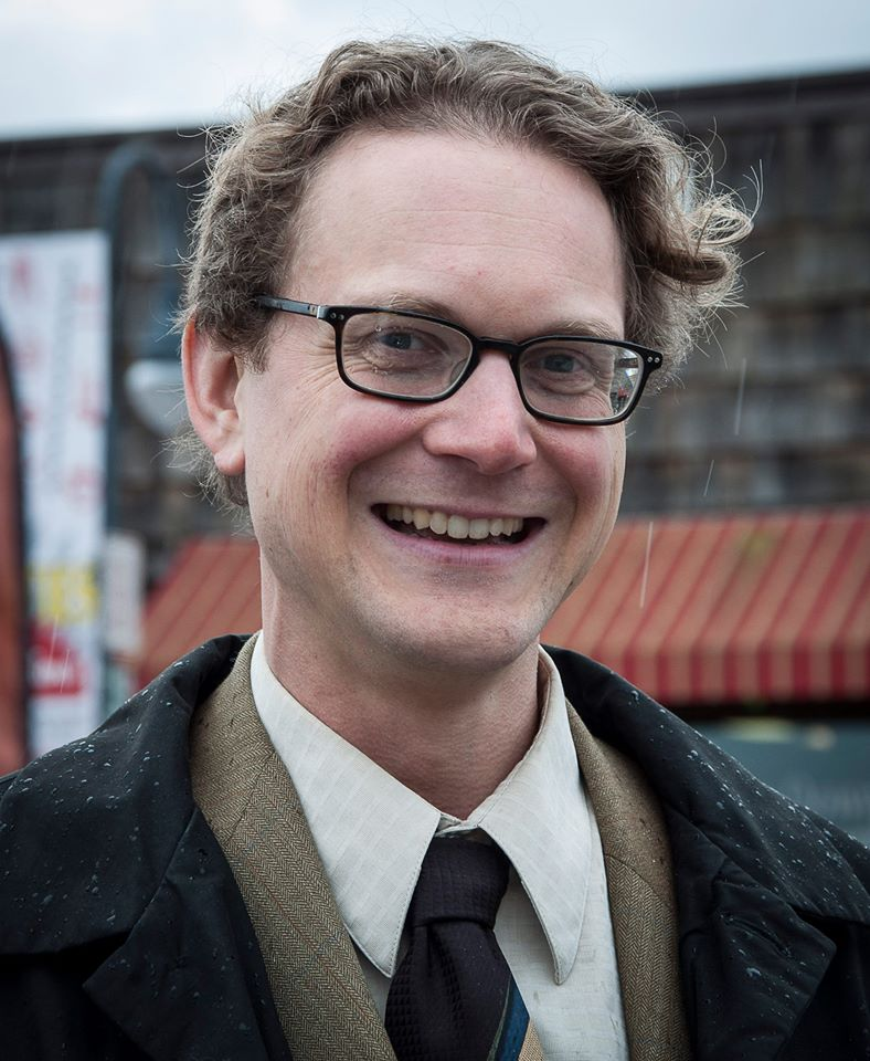 Photo of Lindsey Schromen-Wawrin who has short curly brown hair, is wearing black framed glasses, a brown suit, black coat and tie.