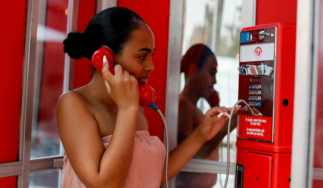 Photo of woman using a red telephone booth. She has dark hair in a bun and a peach blouse.