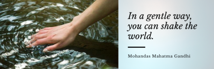 """Hand creating ripples in water and Gandhi quote """"In a gentle way, you can shake the world"""""""